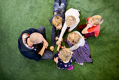 Directly above shot of teacher with students playing on rug in kindergarten - p426m920161f by Maskot