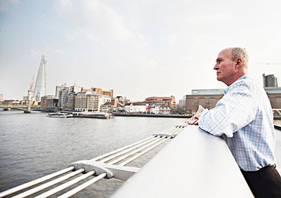 Mature man leaning on Millennium Bridge, London, England, UK - p429m803597f by Liam Norris
