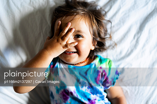 little girl with colorful top lying in bed - p1166m2137297 by Cavan Images