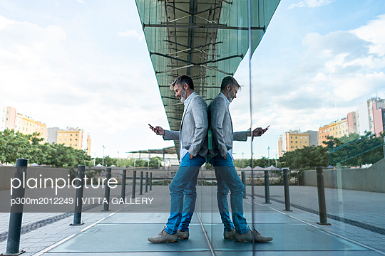 Businessman leaning against glass facade using smartphone - p300m2012249 by VITTA GALLERY