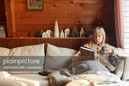 Woman reading book with dog on sofa at home - p924m2091286 by heshphoto