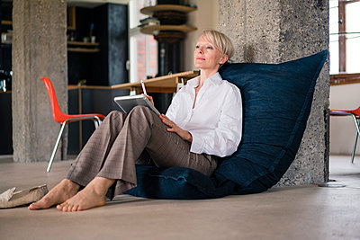 Businesswoman with digital tablet looking away while relaxing on floor chair at home - p300m2266962 by Robijn Page