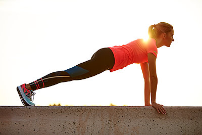 A young athletic woman working out outdoors.  - p343m1184163 by Josh Campbell