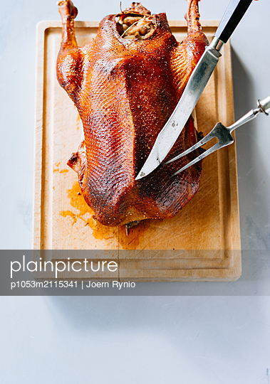 Crispy roasted goose on cutting board - p1053m2115341 by Joern Rynio