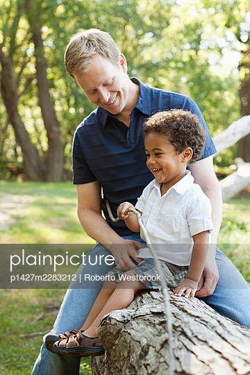 Father and son sitting on log holding twig smiling - p1427m2283212 by Roberto Westbrook