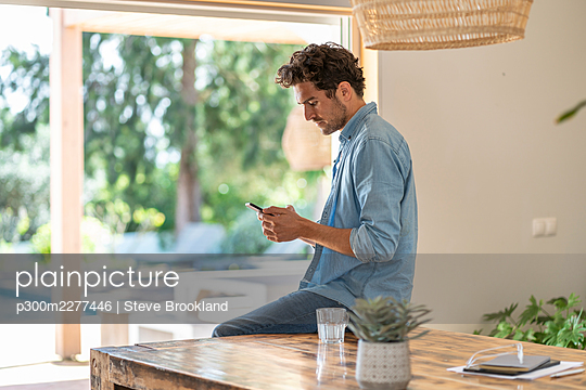 Concentrated man using smart phone while leaning on table - p300m2277446 by Steve Brookland