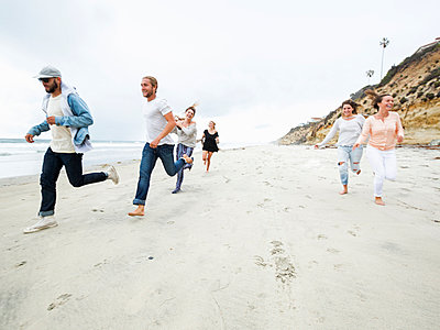 A group of young men and women running on a beach, having fun. - p1100m1038932 by Mint Images