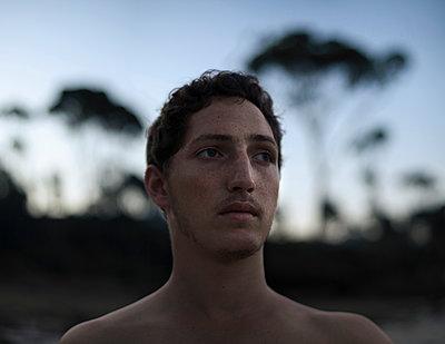 Melancholic young man at twilight - p1324m1165220 by michaelhopf