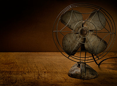 Old metal electric fan on wooden table - p1427m2271626 by Tetra Images/Tom Grill