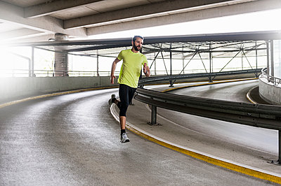 Man running in parking garage in a curve - p300m1587700 by Daniel Ingold