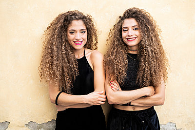 Portrait of laughing twin sisters standing side by side - p300m2060066 by Giorgio Fochesato