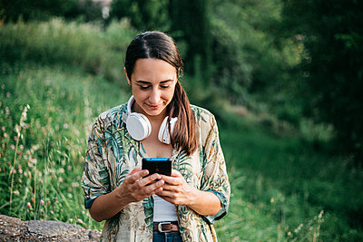 Smiling woman messaging from smart phone at park - p300m2207108 by Xavier Lorenzo