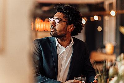Male entrepreneur wearing eyeglasses in cafe looking away - p300m2287709 by Gustafsson