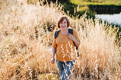 Smiling senior woman hiking during sunny day - p300m2293398 by Eva Blanco