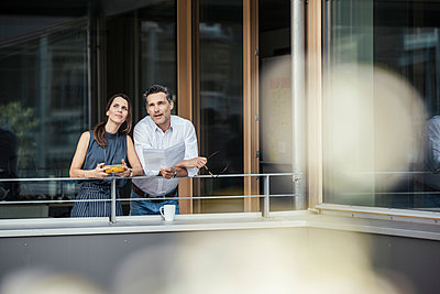 Male and female professionals contemplating while leaning on railing - p300m2293855 by Uwe Umstätter