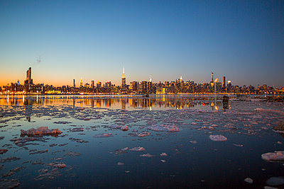 A view of a city across a river in winter. - p343m1088995 by Mat Rick