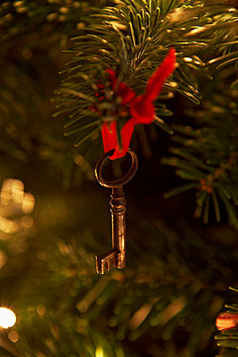 Antique key hanging from Christmas tree in London home UK - p349m695300 by Jon Day