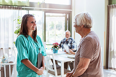 Young nurse talking with senior woman at nursing home - p426m2072547 by Kentaroo Tryman