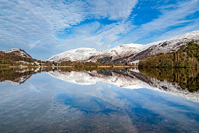 A perfect reflection of snow covered mountains and dramatic sky in the still waters of Grasmere, Lake District National Park, UNESCO World Heritage Site, Cumbria, England, United Kingdom, Europe - p871m2003569 by Martin Child