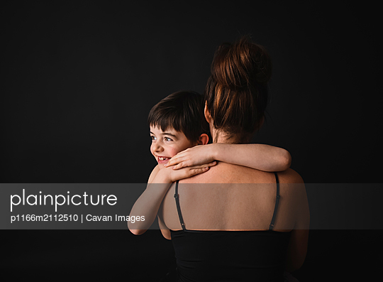 Portrait of young boy hugging mother against black background. - p1166m2112510 by Cavan Images