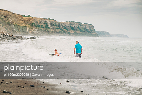 Father and son boogie boarding at the beach - p1166m2208048 by Cavan Images