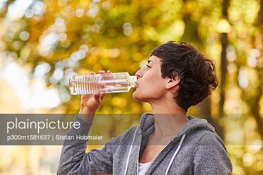 Woman drinking from water bottle - p300m1581637 von Stefan Hobmaier