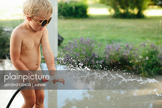 Girl playing with garden hose - p312m2120439 by Johner