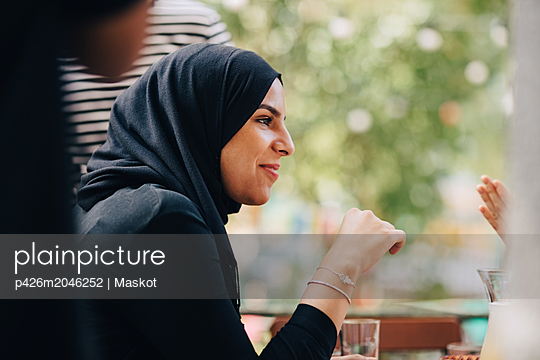 Young woman in hijab looking away while sitting at balcony during party - p426m2046252 by Maskot