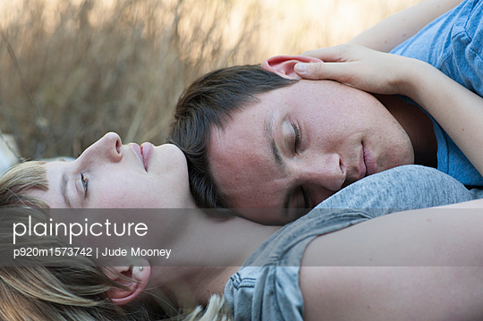Young couple lying together - p920m1573742 by Jude Mooney