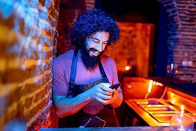 Young man, working in bar, using smartphone - p300m2160073 von Jesús Martinez