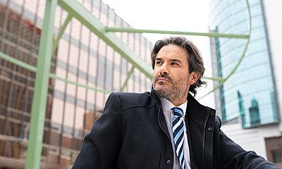 Male entrepreneur looking away against building - p300m2277222 by Jose Carlos Ichiro
