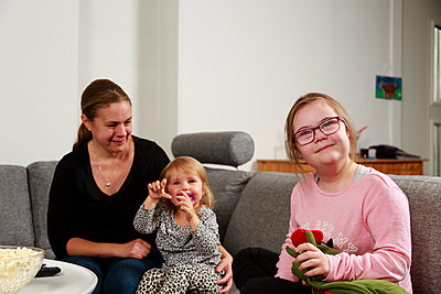 Mother with daughters on sofa - p312m2162283 by Phia Bergdahl
