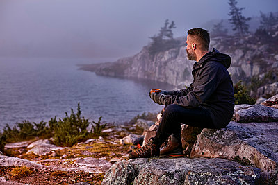 Hiker relaxing with coffee on cliff top, Sarkitunturi, Lapland, Finland - p429m1188174 by Aleksi Koskinen