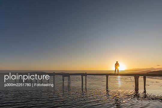 Silhouette of woman standing alone on coastal jetty at sunrise - p300m2251780 by Fotofeeling