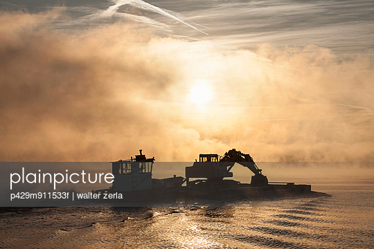 Silhouette of excavator on barge,  Lake Maggiore, Stresa, Piemonte, Italy - p429m911533f by WALTER ZERLA