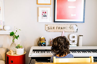 Back view of child playing piano on smart keyboard at home - p1166m2095847 by Cavan Images