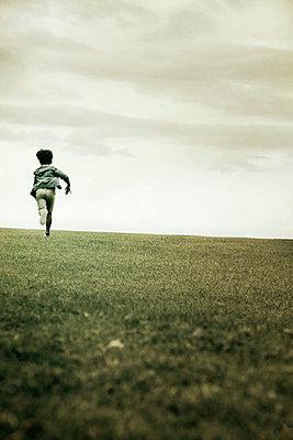 Junge läuft einen Hügel hinauf - p1248m1526408 von miguel sobreira
