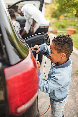 Side view of boy charging electric car while standing on driveway - p426m2072385 by Maskot