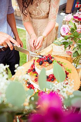 Brautpaar schneidet Hochzeitstorte an - p432m2007495 von mia takahara