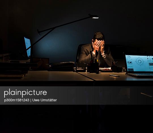 Overstressed businessman sitting at his desk in the dark - p300m1581243 von Uwe Umstätter