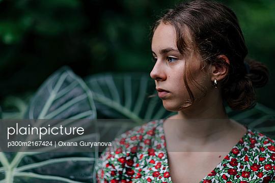 Portrait of female teenager in Botanical Garden, looking sideways - p300m2167424 by Oxana Guryanova