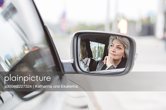 Reflection of businesswoman sitting with colleague on side view mirror - p300m2227324 by Katharina und Ekaterina