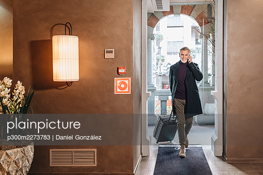 Smiling fashionable man talking on mobile phone while walking with luggage at hotel entrance - p300m2273783 by Daniel González