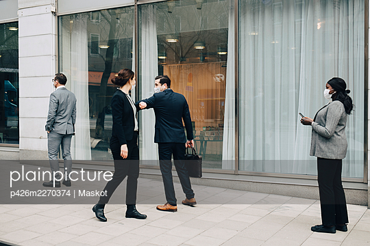 Male and female colleagues greeting with elbow bump on footpath during pandemic - p426m2270374 by Maskot