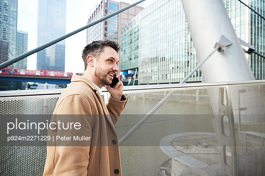 UK, London, Man talking on phone in downtown - p924m2271229 by Peter Muller