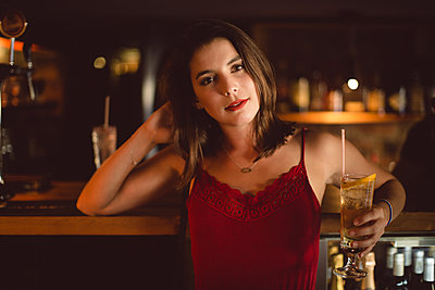 Portrait of beautiful woman holding cocktail glass at counter - p1315m1422085 by Wavebreak