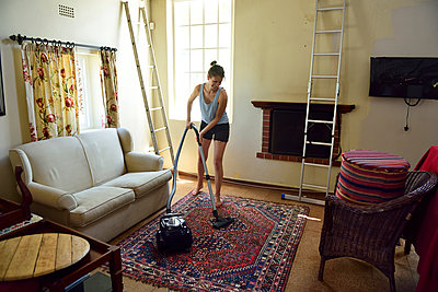 Young woman renovating her home hoovering - p300m2079472 by Eyecatcher.pro