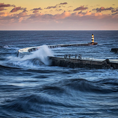 Waves splashing on the pier with a glowing sky at sunset; Seaham, County Durham, England - p442m1482885 by Philip Payne
