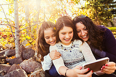 A mom and her two daughters taking a self-portrait while resting during a family outing in a city park on a warm fall day; Edmonton, Alberta, Canada - p442m2101142 by LJM Photo