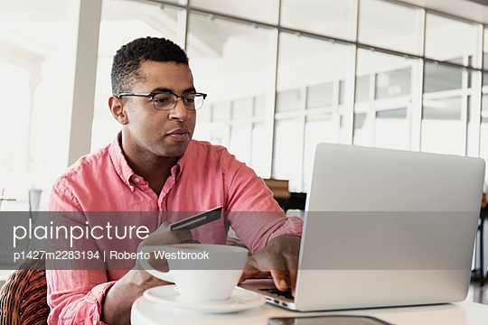 Young man in coffee shop, using laptop, holding credit card - p1427m2283194 by Roberto Westbrook